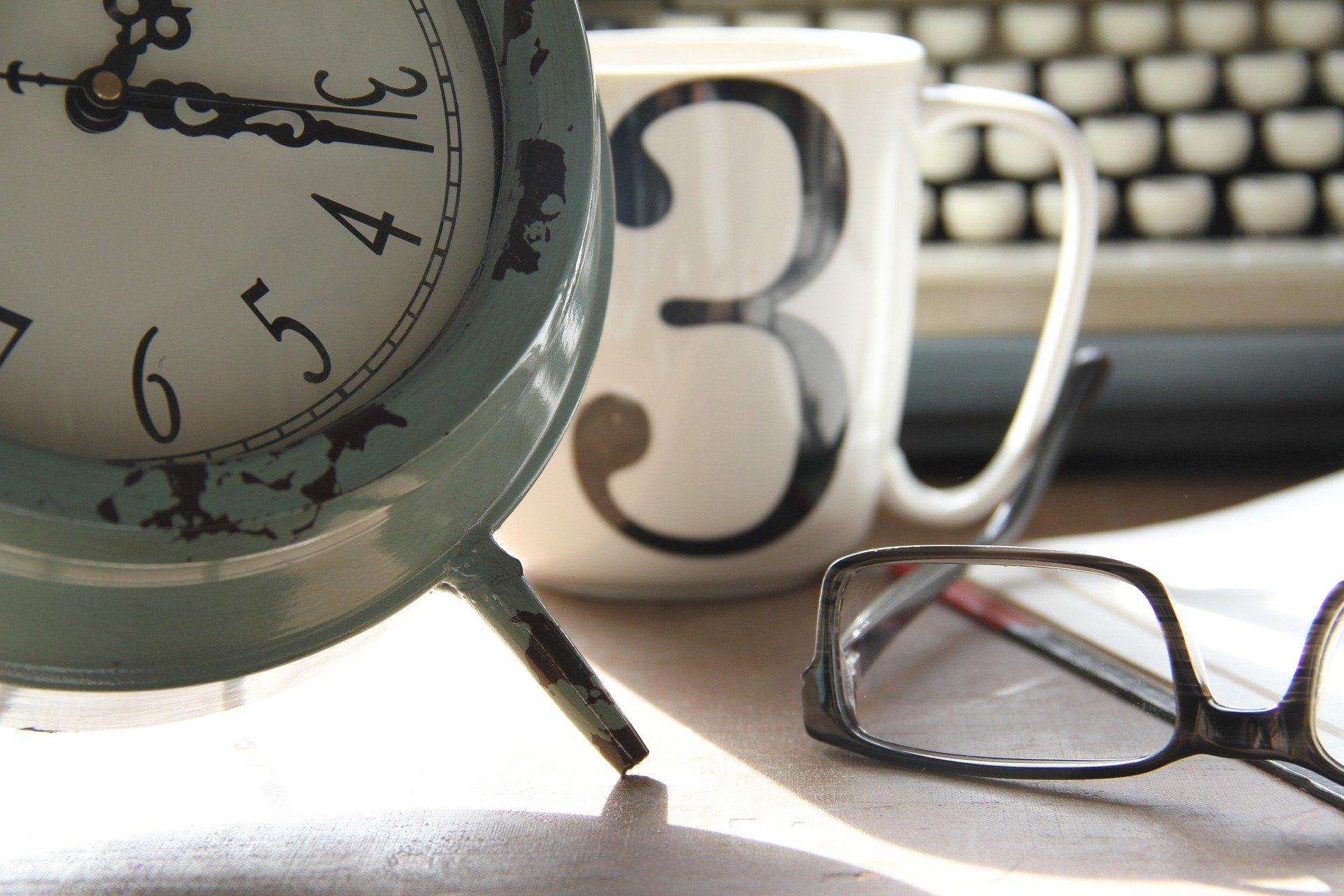 Wecker mit Tasse und Brille
