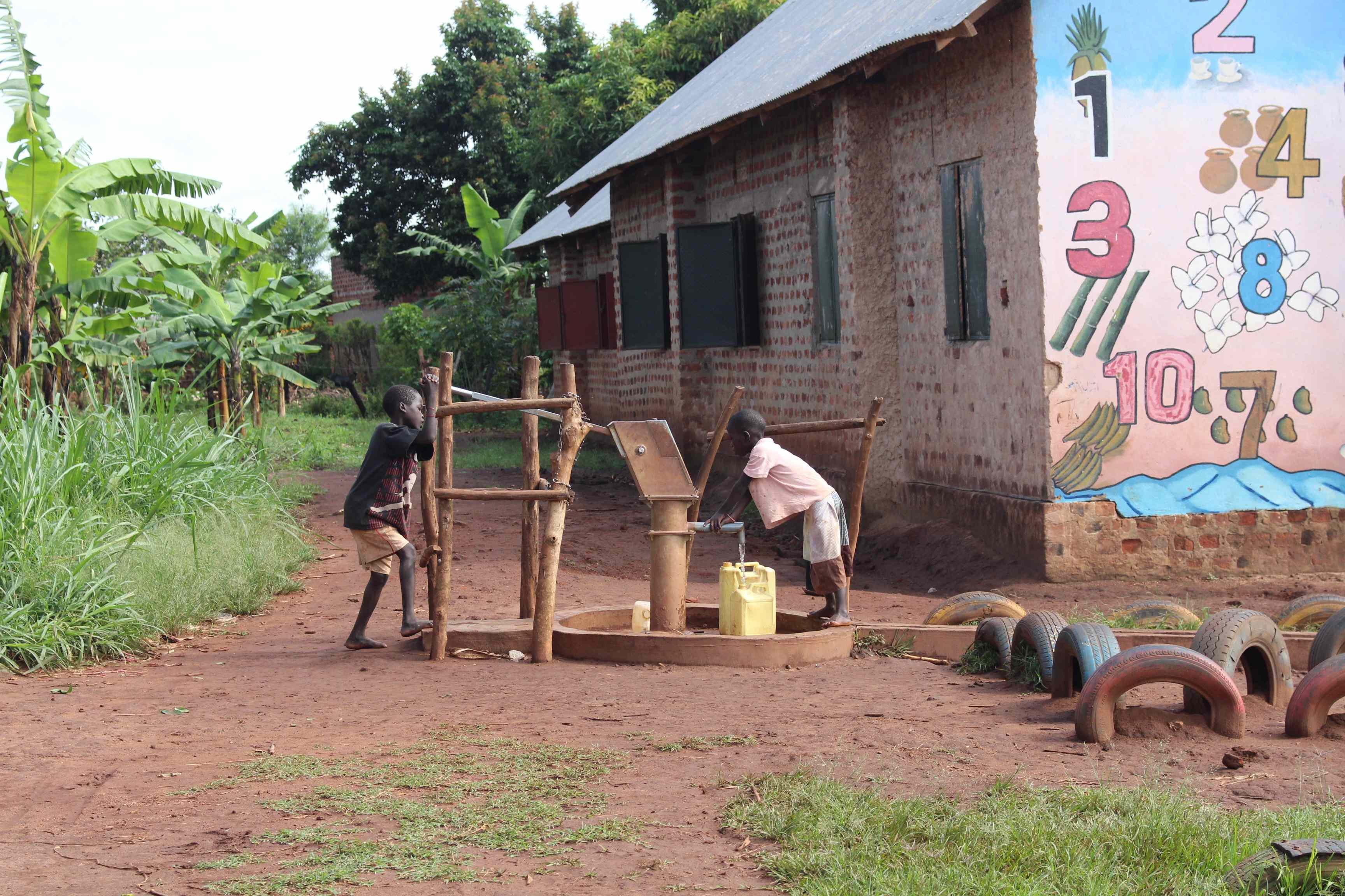 Kinder fördern Wasser aus dem Brunnen.